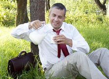 The happy businessman drinks fresh milk Royalty Free Stock Photography
