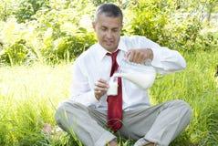 The happy businessman drinks fresh milk Stock Photos