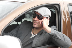 Happy businessman driver talking. Happy male driver smiling while sitting in a car with open front window and talking over mobile phone. Selective focus Royalty Free Stock Images