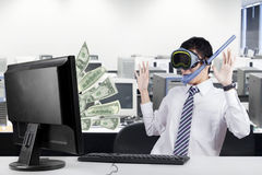 Happy businessman earns money from computer. Surprised businessman wearing goggles and snorkel in the office, earn and looking at the money on the monitor Stock Images