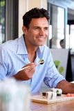 Happy businessman eating sushi at restaurant. Portrait of happy businessman eating sushi at restaurant royalty free stock photography