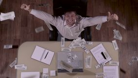 Happy businessman enjoying a successful deal and smiling to the camera while many banknotes fall down stock footage