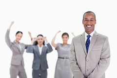 Happy businessman with enthusiastic co-workers in the background. Close-up of a happy businessman smiling with enthusiastic co-workers raising their arms in the Stock Image