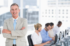 Happy businessman with executives using computers in office Stock Image