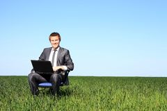 Happy businessman on field, with a laptop Stock Photo