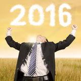 Happy businessman at field with numbers 2016 Royalty Free Stock Photos