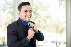 Happy businessman fixing his tie Stock Images