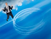 Happy businessman flies in blue sky. Leaving behind a trail of white circles Stock Photo