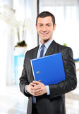 Happy businessman with folder in the office. A happy businessman with blue folder posing in the office Stock Photos
