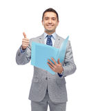 Happy businessman with folder showing thumbs up. Business, people, finances and paper work concept - happy smiling businessman in suit holding folder and showing Stock Images