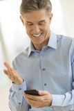 Happy Businessman Gesturing While Reading Text Message Stock Photography