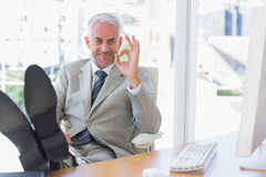 Happy businessman giving ok sign with feet up Stock Photography
