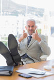 Happy businessman giving thumbs up with feet up Royalty Free Stock Photos