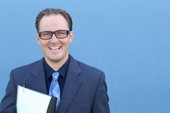 Happy businessman with glasses holding documents isolated on blue looking satisfied. Smiling with satisfaction Stock Images