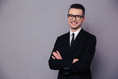 Happy businessman in glasses standing with arms folded Stock Image