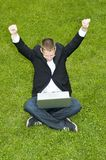 Happy businessman on the grass with laptop Royalty Free Stock Photos