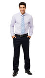 Happy Businessman With Hands In Pockets. Full length portrait of happy businessman with hands in pockets standing against white background. Vertical shot Stock Photography