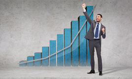 Happy businessman with hands up near graph. Business, office, growth or success concept - happy businessman with hands up celebrating victory in front of the Stock Photos