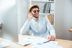 Happy businessman in hat talking on mobile phone in office Stock Image