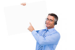 Happy businessman with headphone presenting a panel Royalty Free Stock Photos
