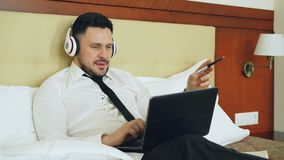 Happy businessman in headphones working at laptop computer and listening music smiling while lying in bed at hotel room stock video