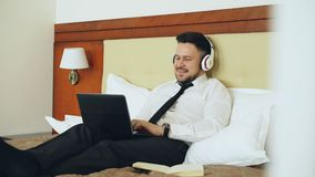 Happy businessman in headphones working at laptop computer and listening music smiling while lying in bed at hotel room. Happy cheerful businessman in headphones stock video