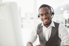 Happy businessman with headset interacting. In his office Stock Photos