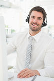 Happy businessman with headset interacting. In his office Royalty Free Stock Photography