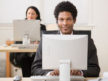 Happy businessman in headset working on computer Stock Photography