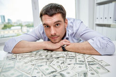 Happy businessman with heap of money in office Royalty Free Stock Photo