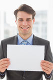 Happy businessman holding blank page. In the office Stock Image