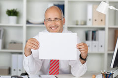 Happy Businessman Holding Blank Paper At Desk. Portrait of happy businessman holding blank paper at office desk Royalty Free Stock Images