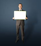 Happy businessman holding blank white card. In his hands Royalty Free Stock Images