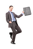 Happy businessman holding a briefcase and gesturing happiness Royalty Free Stock Photo