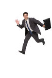 Happy businessman holding a briefcase and running Stock Photos