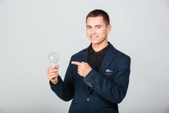 Happy businessman holding bulb Stock Photo