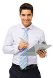 Happy Businessman Holding Clipboard And Pen Royalty Free Stock Photo