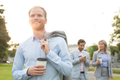Happy businessman holding disposable cup with colleagues standing in background Stock Photos