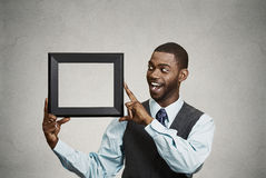 Happy businessman holding empty picture frame Stock Photos