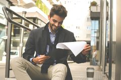 Businessman holding file and reading document on street. stock photography