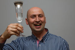 Happy businessman holding glass of champagne over gray background and looking at camera Royalty Free Stock Photography