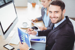 Happy businessman holding graph computer desk Royalty Free Stock Image