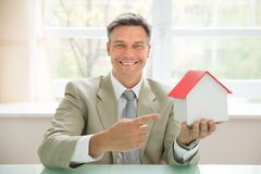 Happy businessman holding house model Royalty Free Stock Image