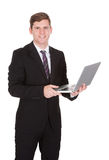 Happy businessman holding laptop Stock Images