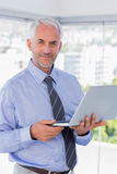 Happy businessman holding laptop. Standing in his office Royalty Free Stock Images