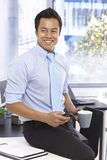 Happy businessman holding mobile and tea mug Royalty Free Stock Photography