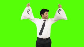 Happy businessman holding money bags on green background stock video footage