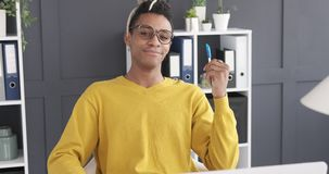 Happy businessman holding a pen at office. Portrait of casual african american businessman smiling while holding a pen at office stock video footage