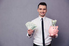 Happy businessman holding pig money box Royalty Free Stock Photos