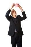 Happy businessman holding piggybank. Smiling mature businessman holding piggybank Royalty Free Stock Image